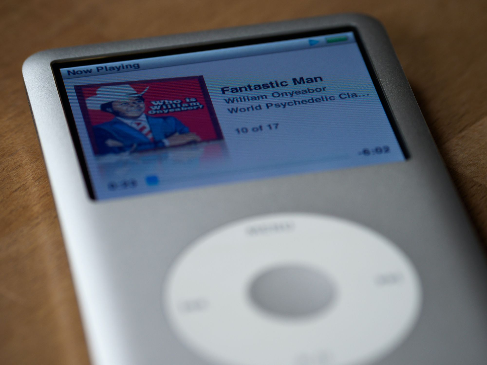 A silver Apple iPod with the scroll wheel and colour screen