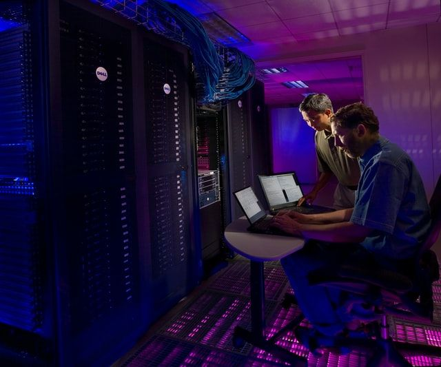Two men in a data centre working on laptops beside several racks of servers